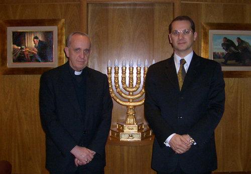 """En el 2006, el entonces """"cardenal"""" Jorge Bergoglio tomándose una foto junto al rabino frente a una menorá dentro de una sinagoga"""